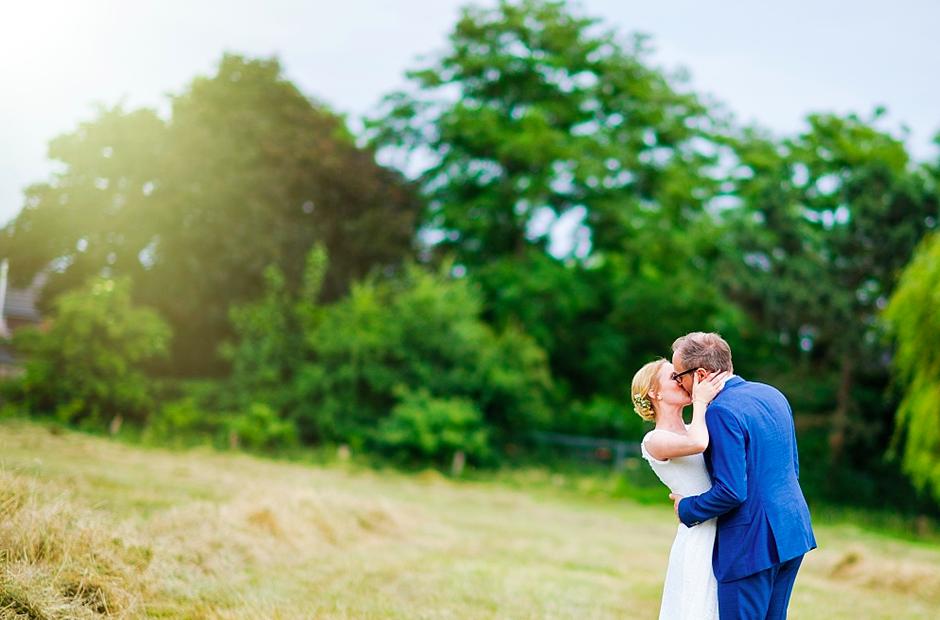 Ein Brautpaar küsst sich auf einer Wiese. Mark Dillon Photographie.