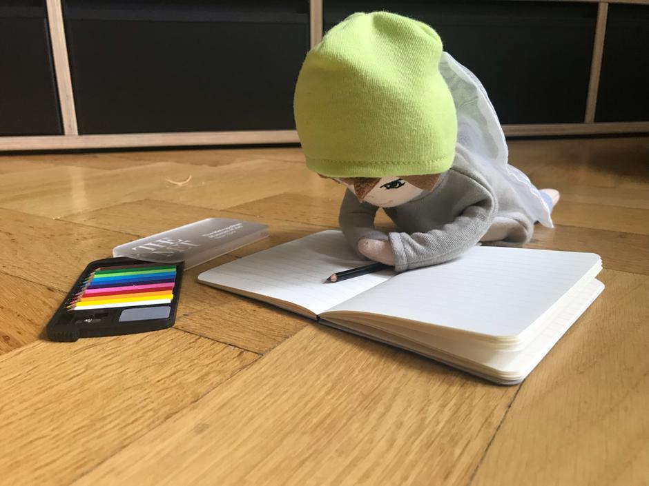 Kleiner Engelspuppe Flauseflocke schreibt in ein Buch mit kleinen Stiften.