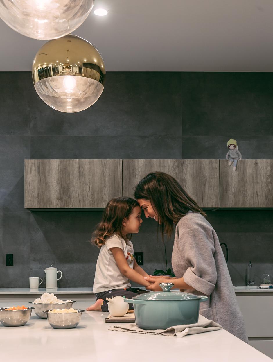 Mama und Kind kochen und ein Flauseflocke Engel sitzt auf dem Regal und schaut zu.