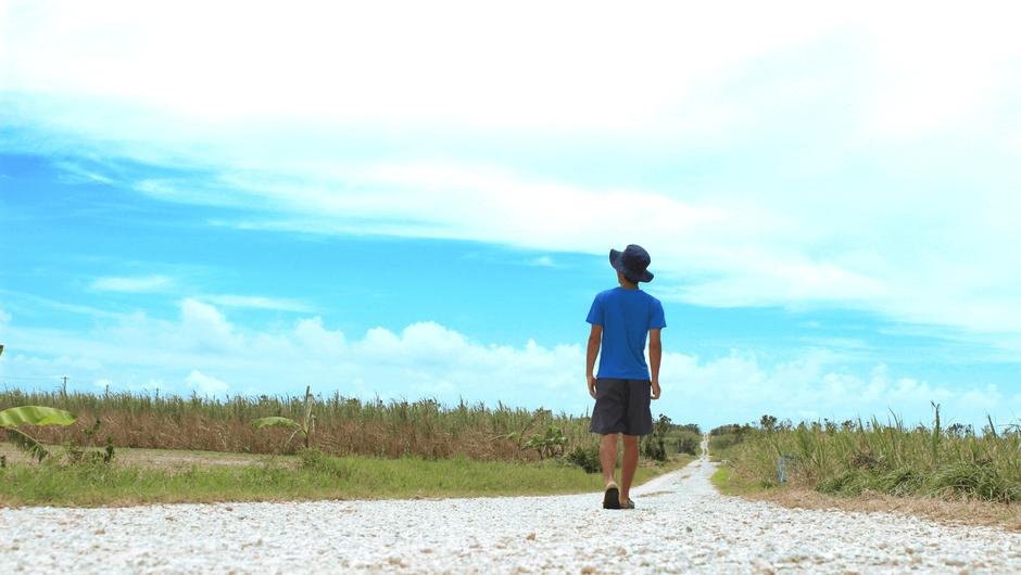 一本道を歩く男性