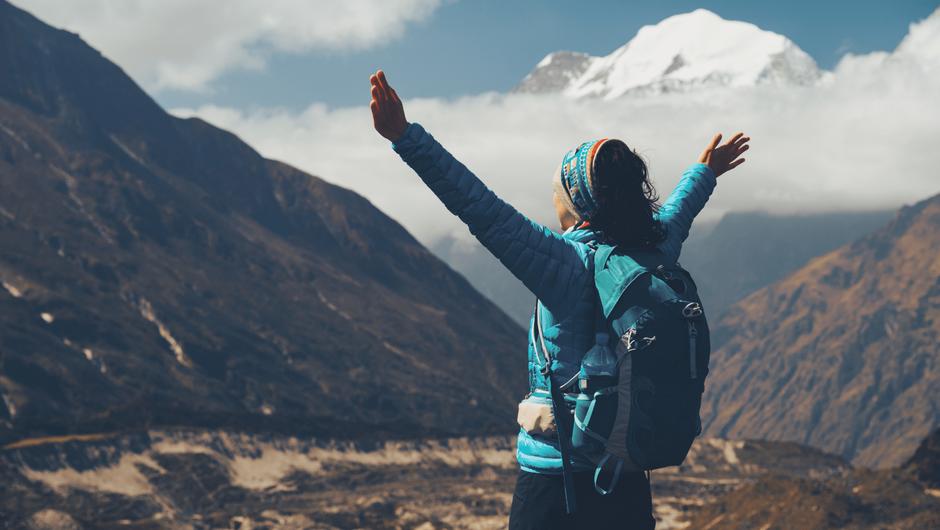 山に向かって両手を上げる登山家