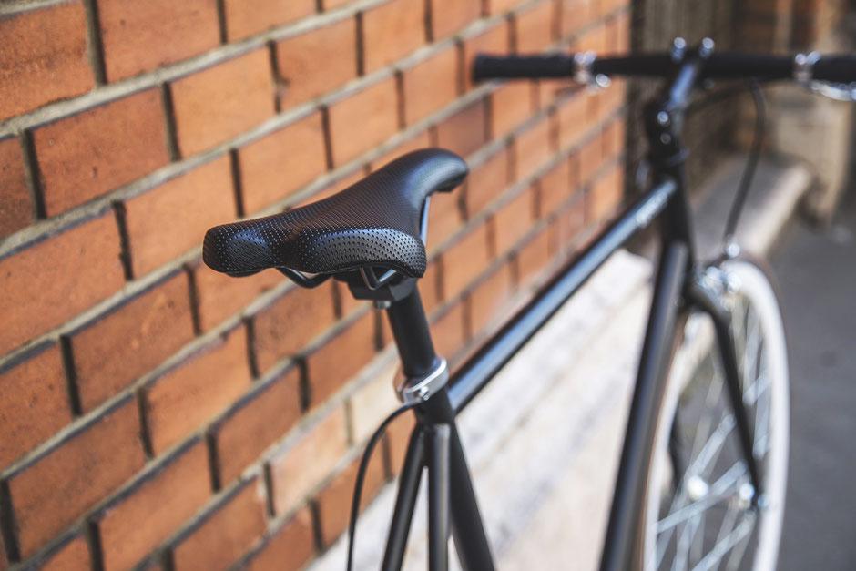 vélo singlespeed noir sur mur en brique