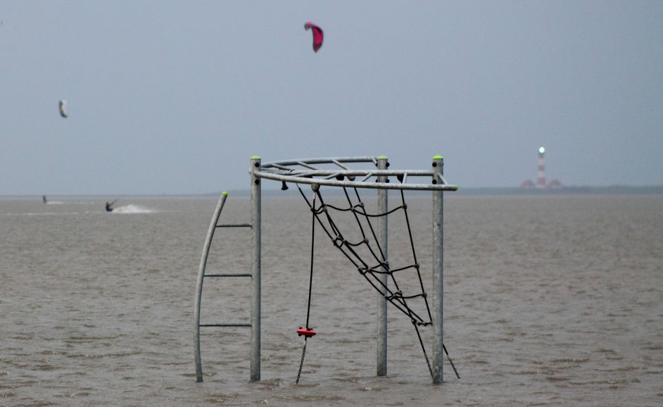 Bild: Sturmflut in St. Peter-Ording: Kitesurfer surfen zwischen Spielgeräten auf dem überfluteten Strand (Foto: Karena Hoffmann-Wülfing)