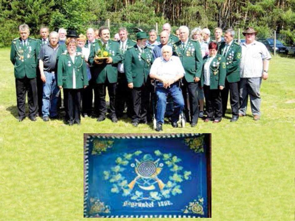 Gruppenbild der Mitglieder bei der 20. Jahresfeier des Schützenvereins und die Vereinsfahne.