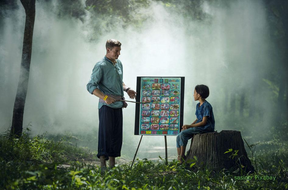 Mann unterrichtet Kind das Alphabet und das Kind hat Freude am Lernen im Regenwald