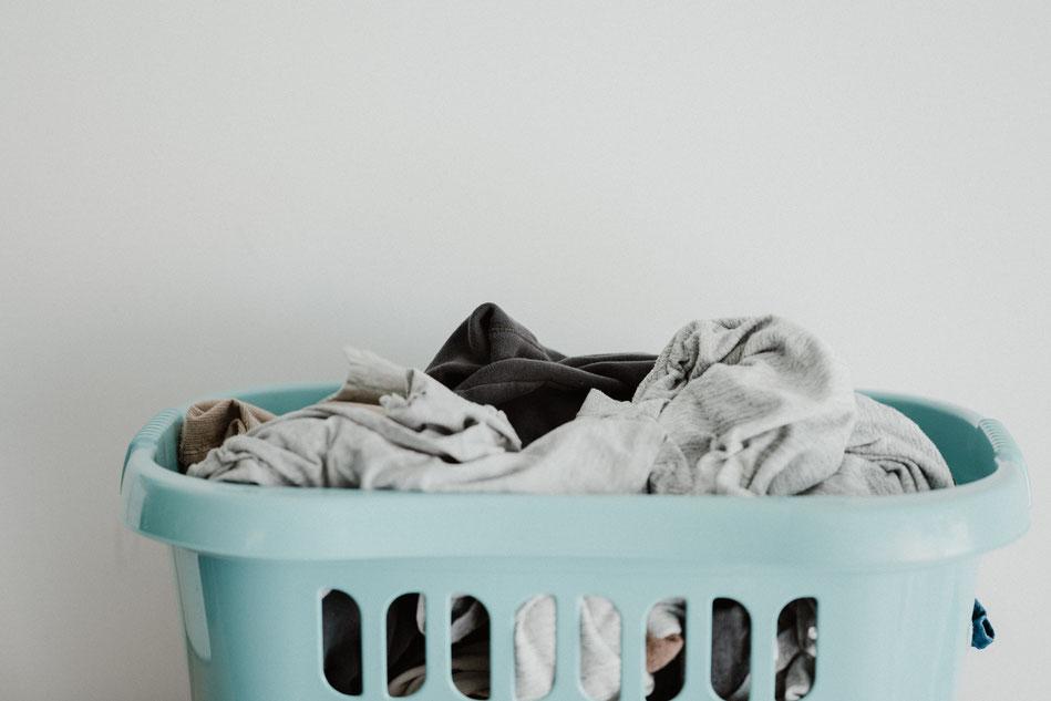 Voller Wäschekorb mit Kleidung aus Synthetik