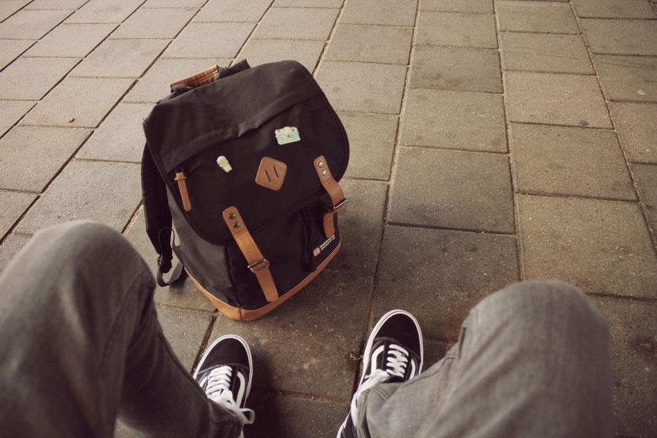 Junger Mann sitzt auf Fußweg mit Rucksack