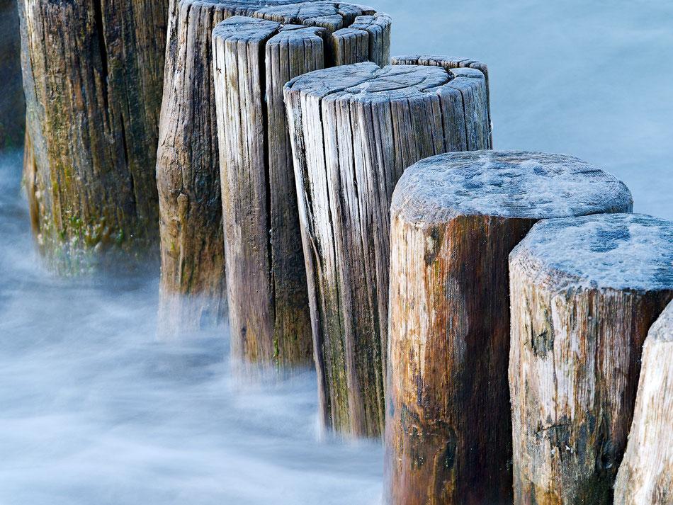 Buhne aus Holzpfählen an der Ostsee. Durch die lange Belichtungszeit erscheint das Wasser wie Nebel.