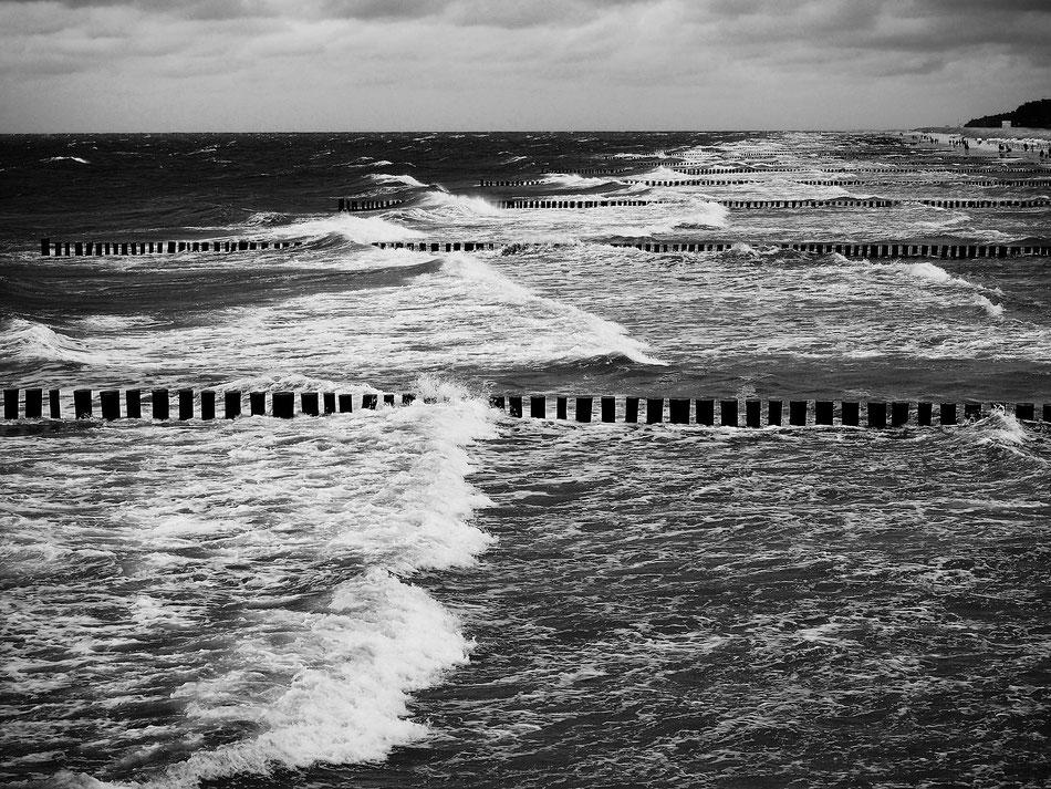 Hohe Wellen brechen sich an langen Buhnenreihen. Am Strand sind einige Menschen.