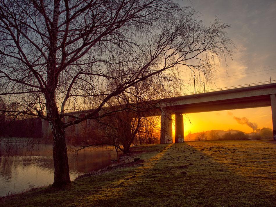 Die ersten Sonnenstrahlen erleuchten das Viadukt und den Bielefelder Obersee