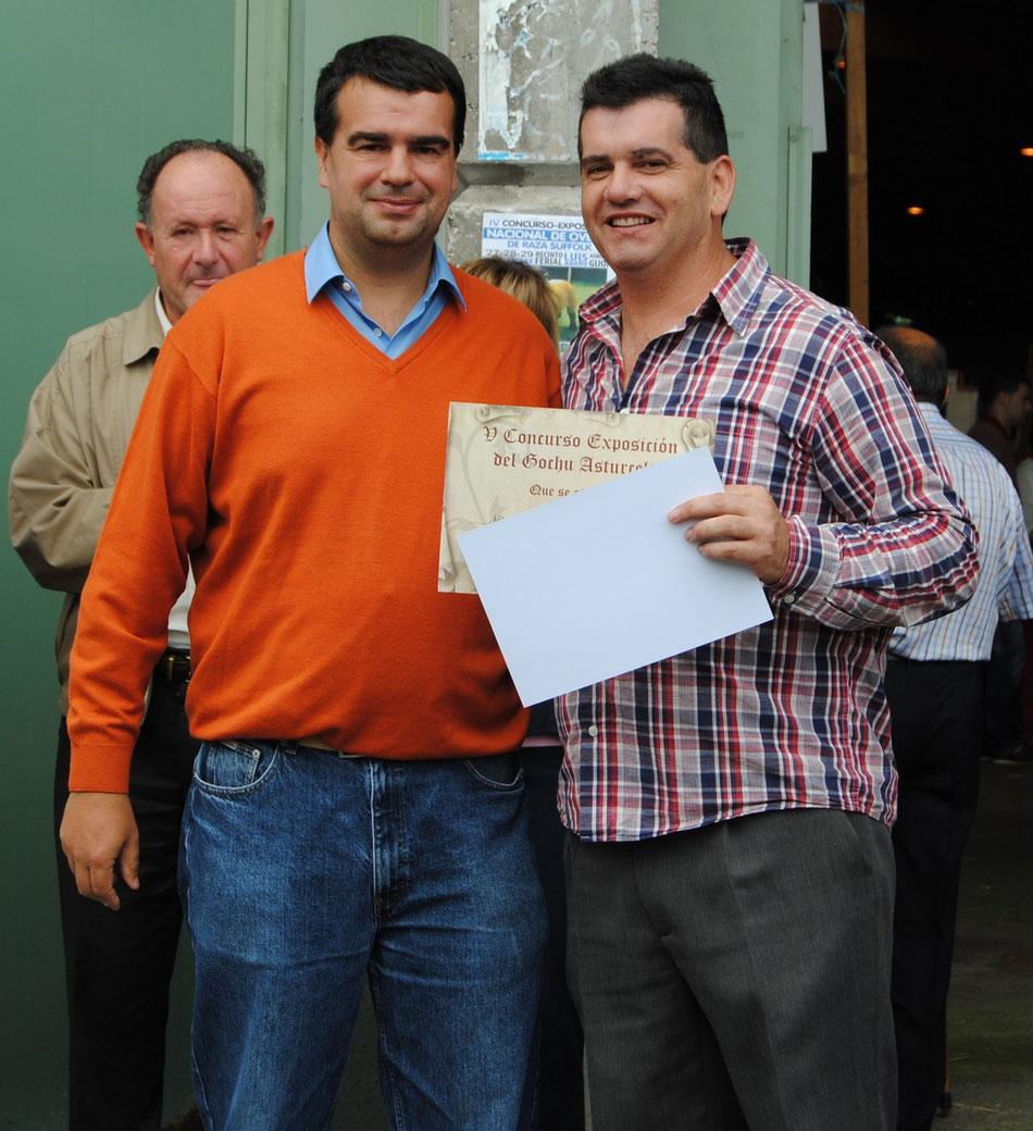 José Manuel Iglesias, presidente de ACGA, hace entrega del primer premio a la mejor gocha al hijo de la ganadera María del Rosario Sánchez, que además se llevó el segundo premio al mejor llabascu y mejor gocha con gochinos