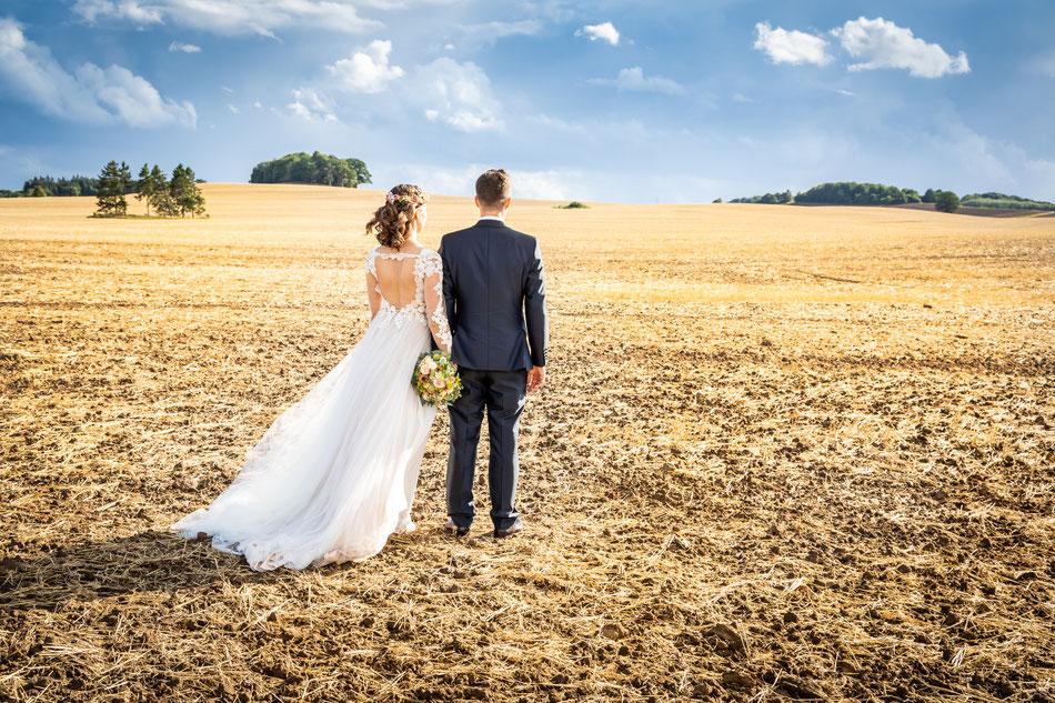 Hochzeitsfoto im Feld der Lüneburger Heide, Hochzeitsfotos Feld Schleswig Holstein, Hochzeitsbilder auf dem Feld Mecklenburg Vorpommern und Schleswig Holstein, Hochzeitsfotograf Dennis Bober.