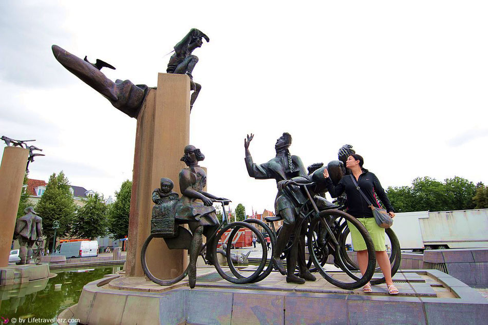 Posieren mit einer Skulptur in Brügge