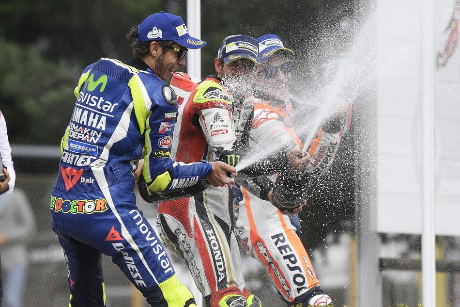 Sieger unter sich. Cal Crutchlow lässt mit Valentino Rossi und Marc Marquez die Champagnerkorken knallen.