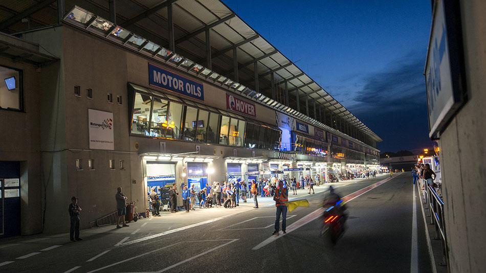 Foto der Boxengasse der Motorsportarena Oschersleben während der Speedweek 2016 bei Nacht