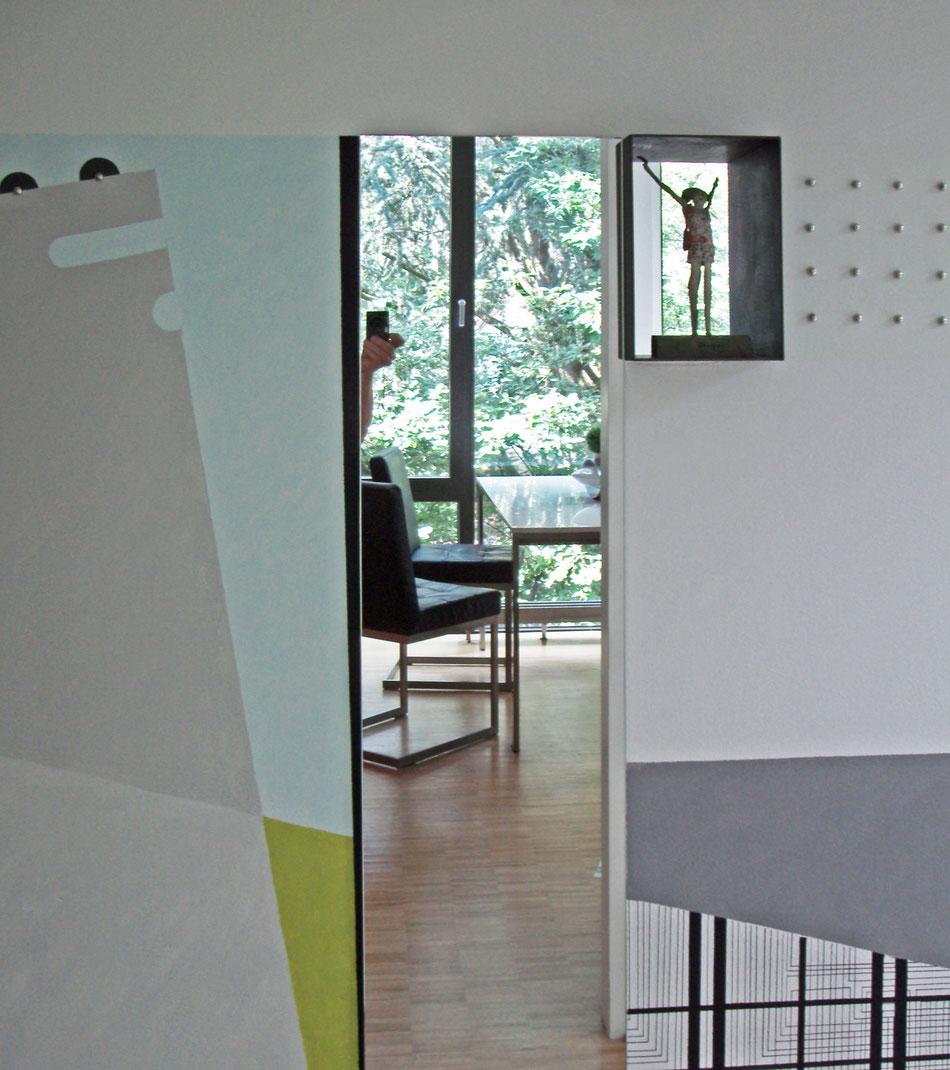 Wandgestaltung aus nachleuchtenden Farben, Spiegeln und Ziernägeln.