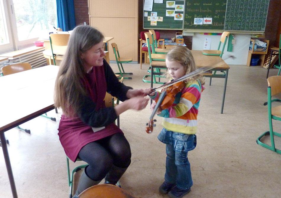 Heike Prange gibt einem interessierten Mädchen das erste Mal eine Geige in die Hand.