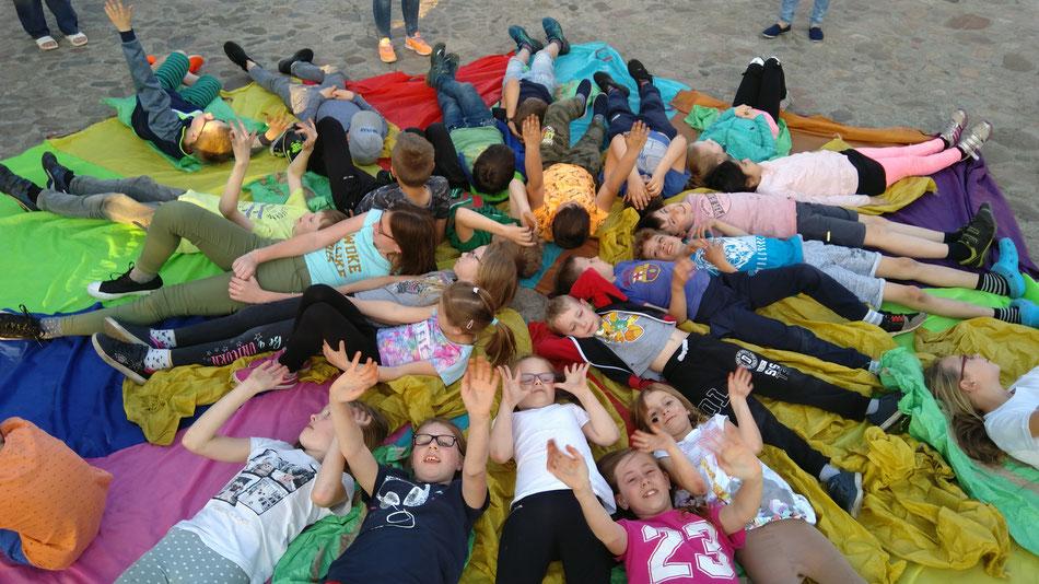 ...und spielten die Kinder miteinander zusammen unter und auf (u.A.) dem farbigen Fallschirm...