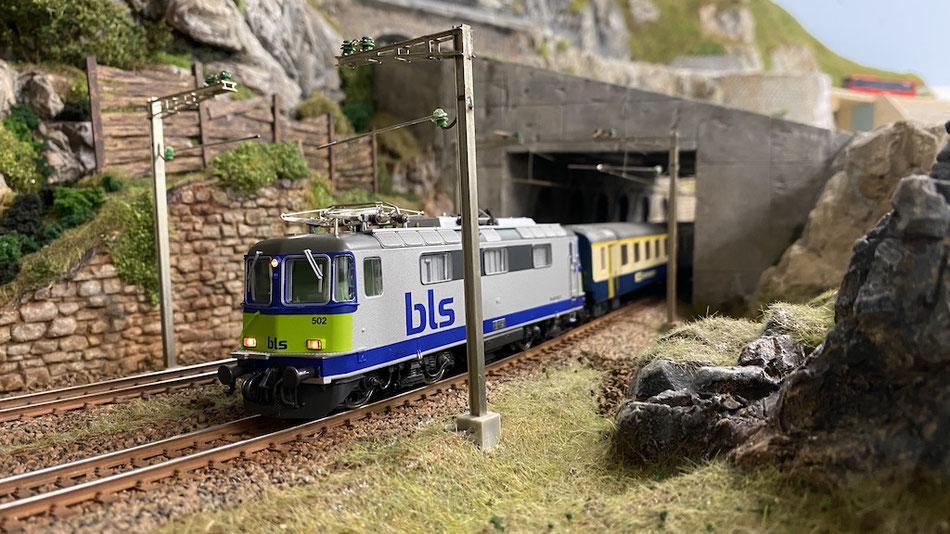 """BLS Re 4/4 im Nina-Design, im Hintergrund die im Mai 2020 erstelle """"Lawinen-Schutzgalerie"""""""