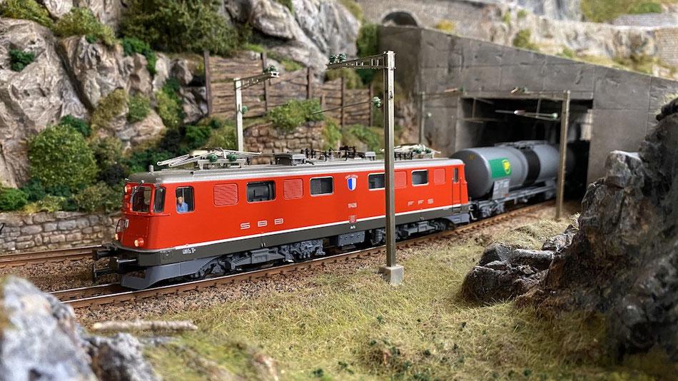 """Die Ae 6/6 """"Luzern"""" (Modell von Hag) befördert einen Kesselwagen-Zug über die Bergstrecke"""