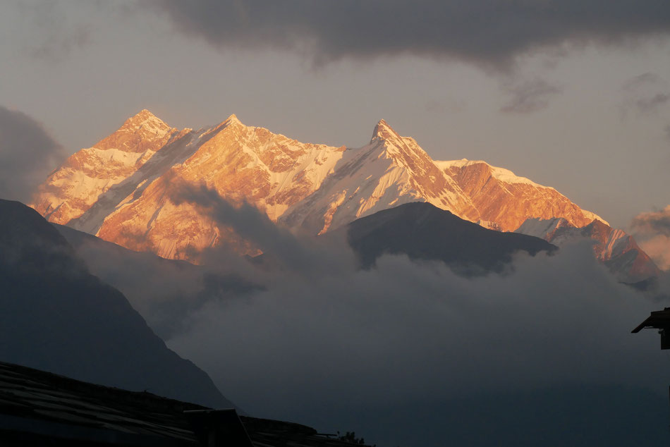 Von Wolken gerahmte Berggipfel im Sonnenschein