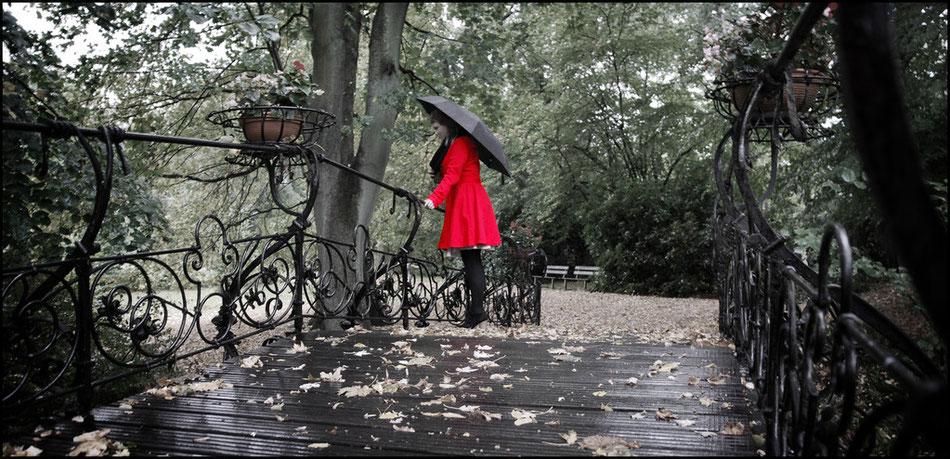 roter mantel im regen auf einer brücke auf dem ohlsdorfer friedhof
