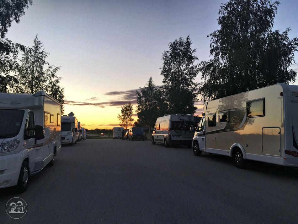 Mit dem Wohnmobil nach Norwegen, Zwischenstopp in Schweden am Stellplatz, Wohnmobile auf dem Stellplatz im Sonnenuntergang