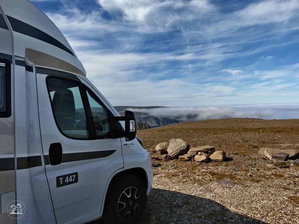 Mit dem Wohnmobil ans Nordkapp in Norwegen, Blick seitlich am Wohnmobil Carado T477 vorbei auf dem Parkplatz des Nordkapps Richtung Abgrund und Felsen und Wolken