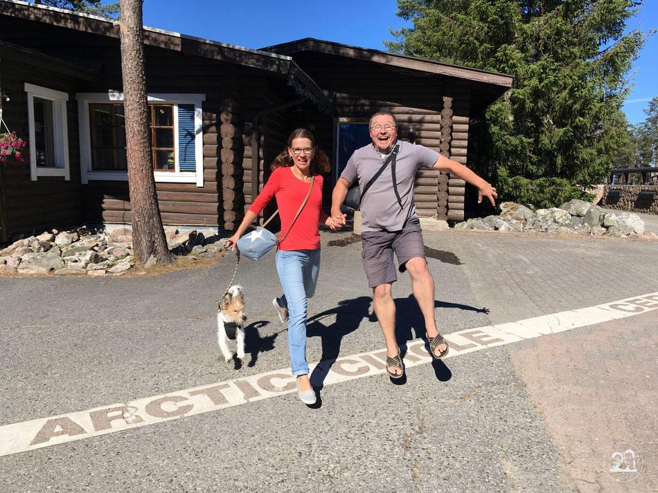 mit dem Wohnmobil nach Norwegen, Überquerung des nördlichen Polarkreises in Finnland im Weihnachtsdorf, Leni und Toni mit Kromfohrländer Hund Clara springen gemeinsam über den Polarkreis