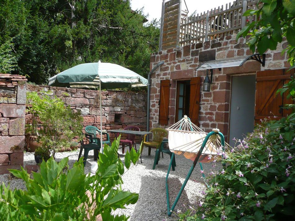 en Vallée de la Dordogne, la Mérelle de Collonges-la-Rouge a sa terrasse avec hamac, chaises longes, parasols
