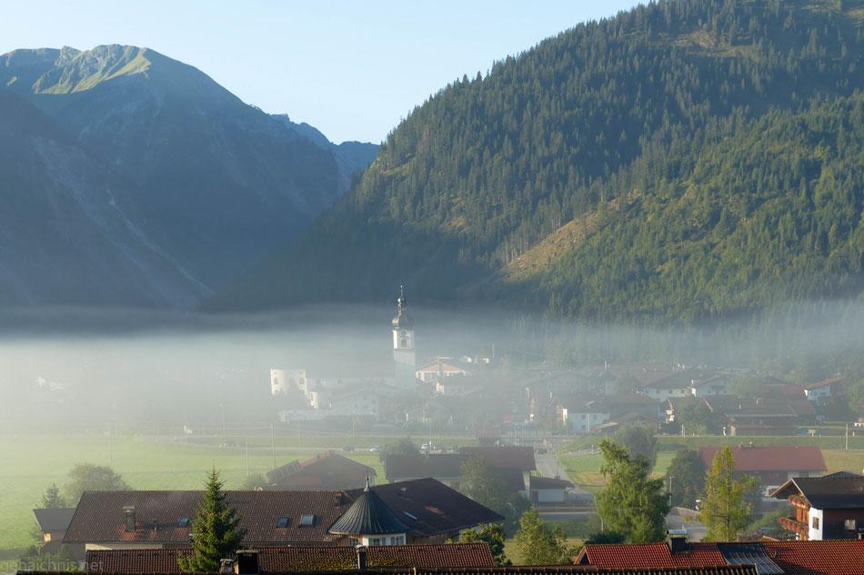 Die Sonne vertreibt den Morgennebel, welcher Tannheim und die Pfarrkirche mehr und mehr frei lässt