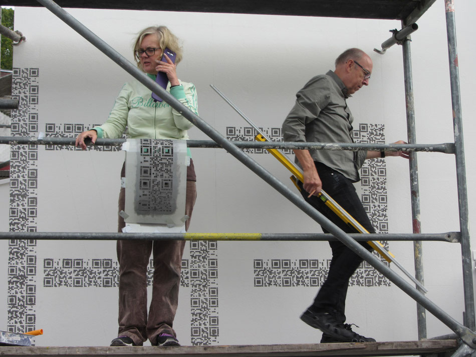 Die Bauherrin Christa Lauterbach und der Künstler Werner Krömeke. Das ehemalige Fachwerk wird durch QR-Codes dargestellt.