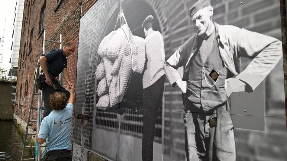 Aludibondplatten mit Motiven von Hafenarbeitern bedruckt