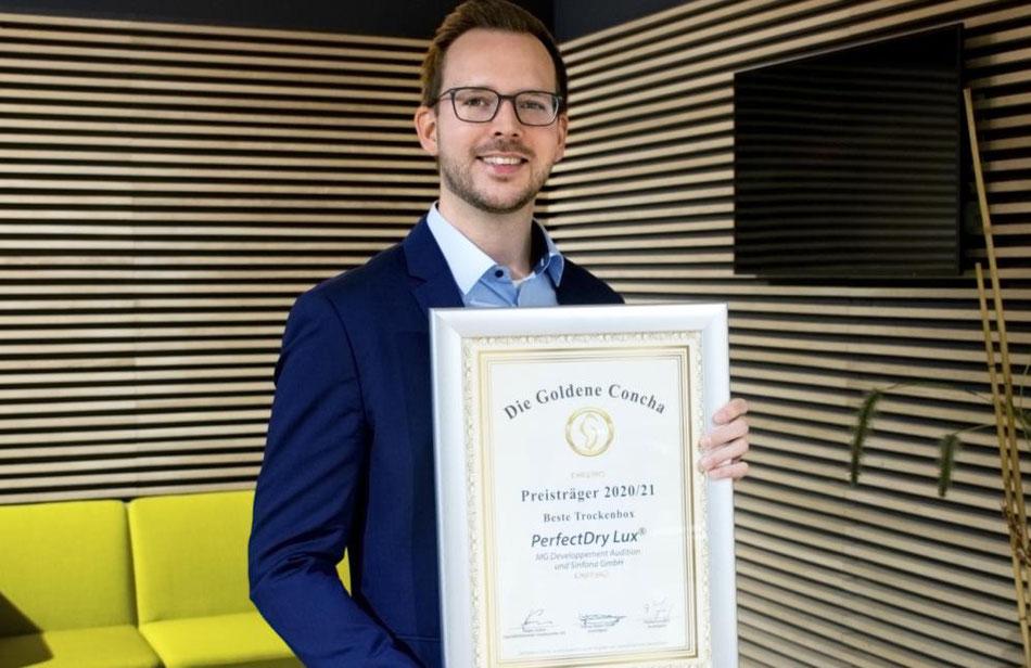 Michael Becker (Marketing & Vertrieb) präsentiert die Siegerurkunde für die beste Trockenbox (Sinfona).