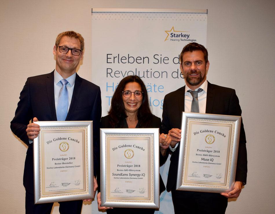 Große Freude beim dreifachen Gewinner Starkey, für den Markus Böcker (Geschäftsführer) und Karl Beck (Leiter Marketing und Vertrieb) die Siegerurkunden von Tannassia Reuber (Geschäftsführerin Individual Akustiker Service) entgegen nahmen.