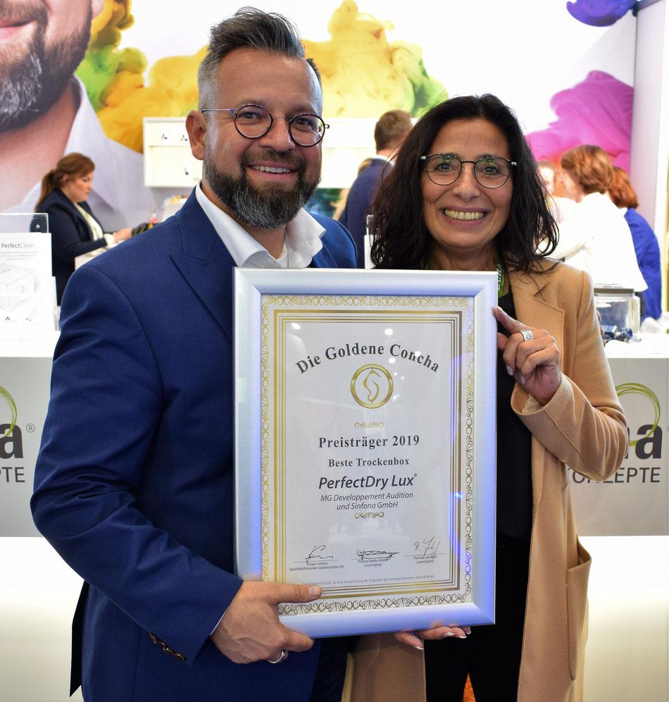 Thomas Häusler (Geschäftsführer der Sinfona GmbH) freut sich über die Auszeichnung als Tannassia Reuber (Geschäftsführerin der Individual Akustiker Service GmbH) ihm die Siegerurkunde überreicht.