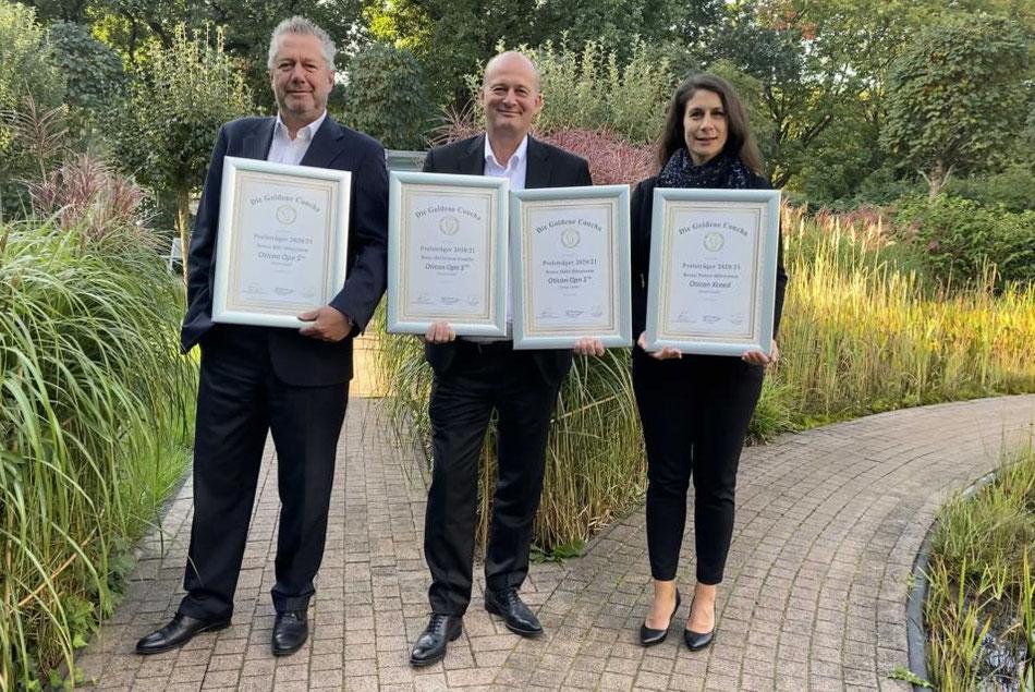 Oticon Vertriebsleiter Wolfgang Weber (lks.), Marketing-Leiterin Sonja Grazia D'Introno (re.) und Geschäftsführer Torben Lindoe (Mitte) freuen sich über vier Siegerurkunden in diesem Jahr.
