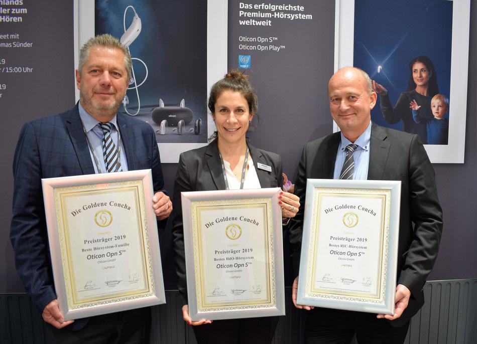 Oticon Vertriebsleiter Wolfgang Weber (lks.), Marketing-Leiterin Sonja Grazia D'Introno (Mitte) und Geschäftsführer Torben Lindoe (re.) freuen sich über die Siegerurkunden auf der EUHA in Nürnberg.