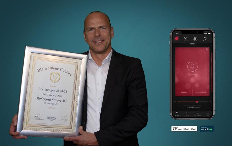 Geschäftsführer Jochen Meuser von GN Hearing aus Münster zeigt erfreut die Siegerurkunde für die beste App.