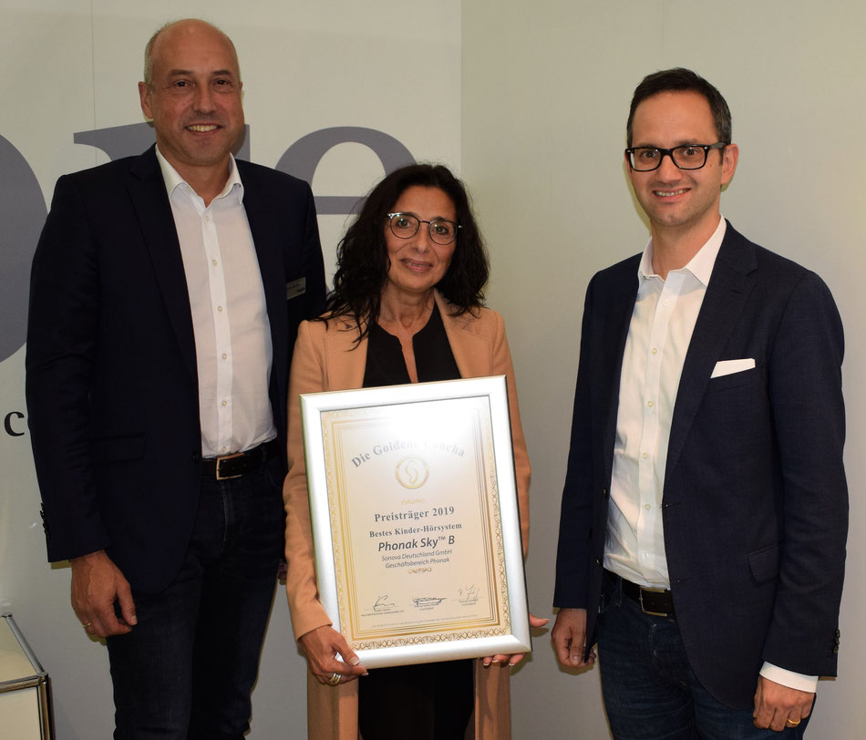 Andreas Tikovsky (Leiter Vertrieb, Geschäftsbereich Phonak, Sonova Deutschland GmbH) und Martin Heierle (Geschäftsführer Sonova Deutschland GmbH) freuen sich über die Siegerurkunde, überreicht durch Tannassia Reuber (Geschäftsführerin IAS).