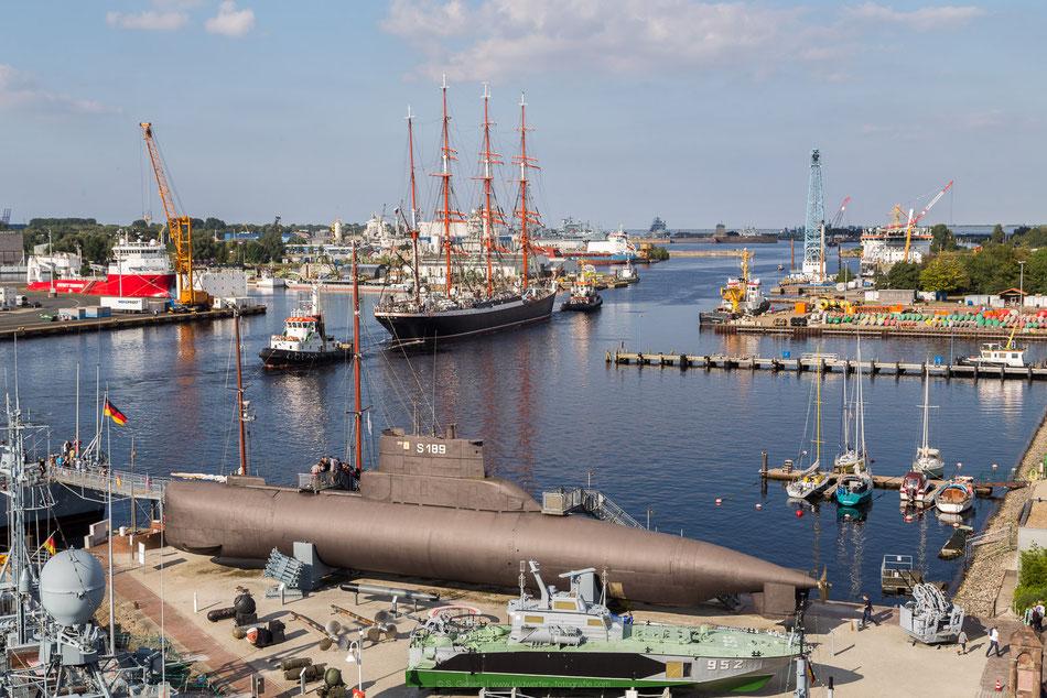Russisches Segelschulschiff Sedov wird von Schleppern durch den Hafen von Wilhelmshaven Richtung Schleuse gezogen, im Vordergrund ist das Deutsche Marinemuseum zu sehen.