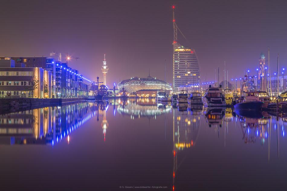 Beleuchtete Havenwelten in Bremerhaven mit dem Klimahaus und dem Atlantic Sail City Hotel.