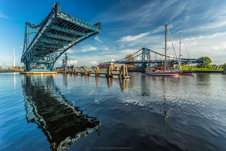 Zwei Segelboote durchqueren die geöffnete Kaiser-Wilhelm-Brücke in Wilhelmshaven bei Sonnenschein und perfekter Spiegelung im Wasser
