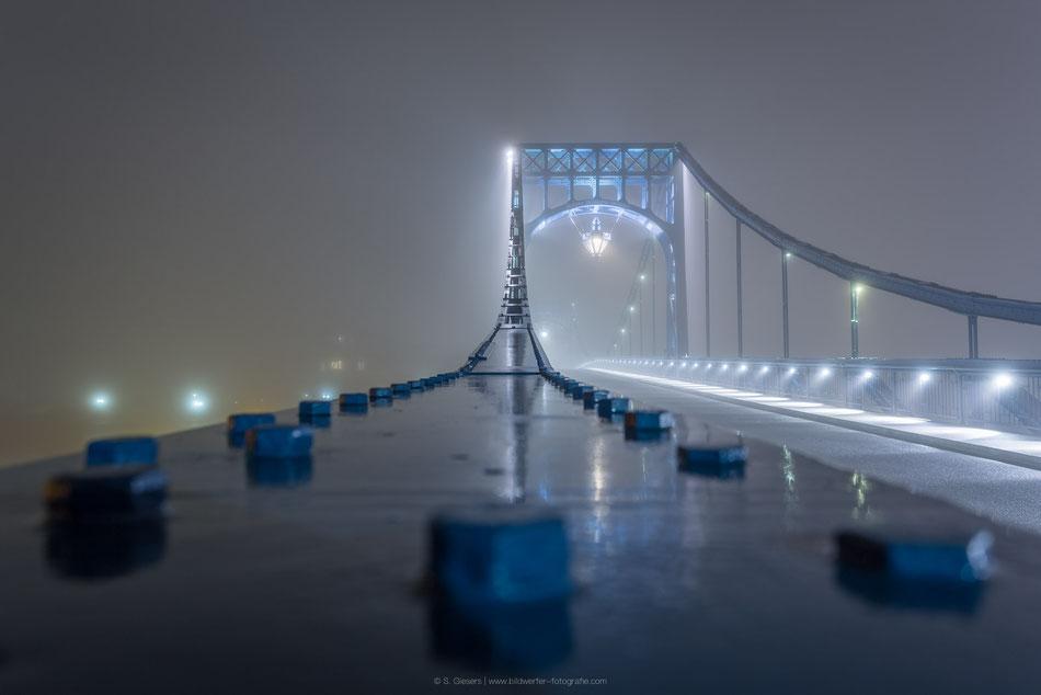 Kaiser-Wilhelm-Brücke bei Nacht und Nebel.