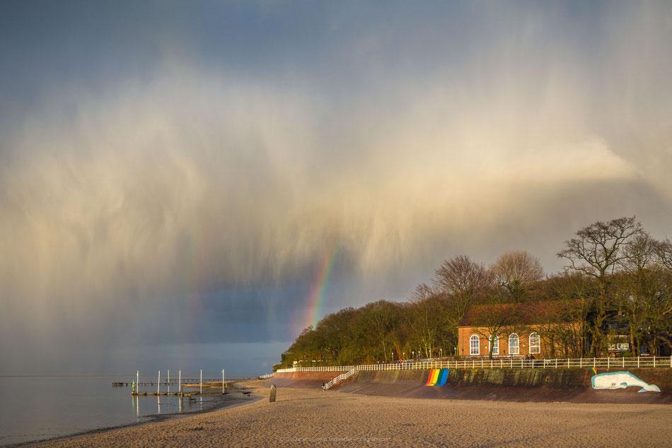 Unwetter und Regenbogen am Strand von Dangast mit dem Kurhaus im Hintergrund.