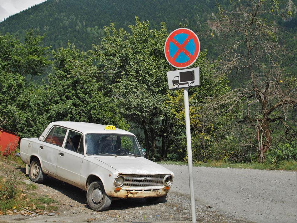 Átlagos állapotú félszemű taxi várja a fuvarját. A mellette lévő leszakadt elejű Micrában (szintén taxis) az öreg szépen húzogatta a vodkásüveget.