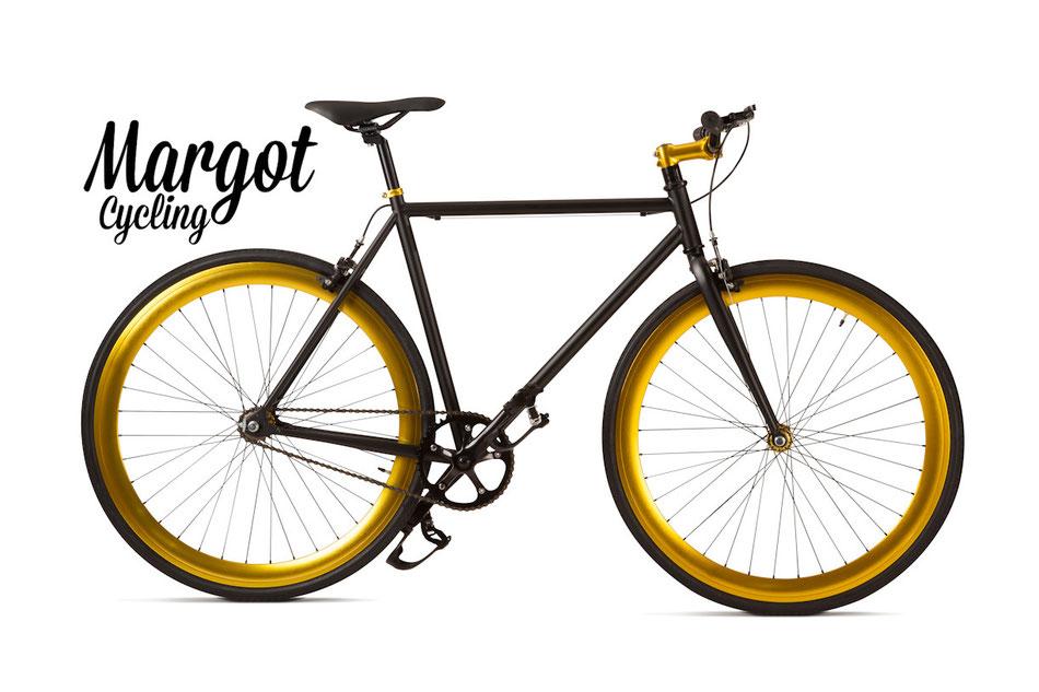 Fixed bike MARGOT ELDORADO. Cuadro negro opáco y partes negras. Resalta el luminoso ORO anodizado de los aros, de la tija de manillar y de los bujes. ¡Luminosa y elegante!