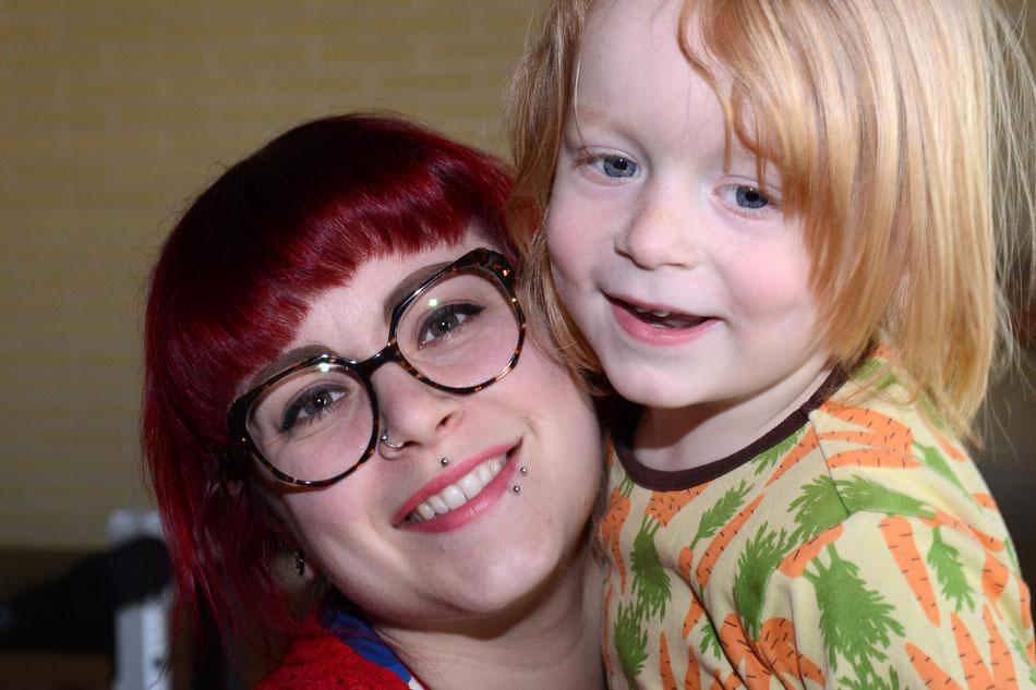 Porträt Anke, rothaarig mit Brille und Piercings mit Noah im T-Shirt mit Karottenmotiv auf dem Arm
