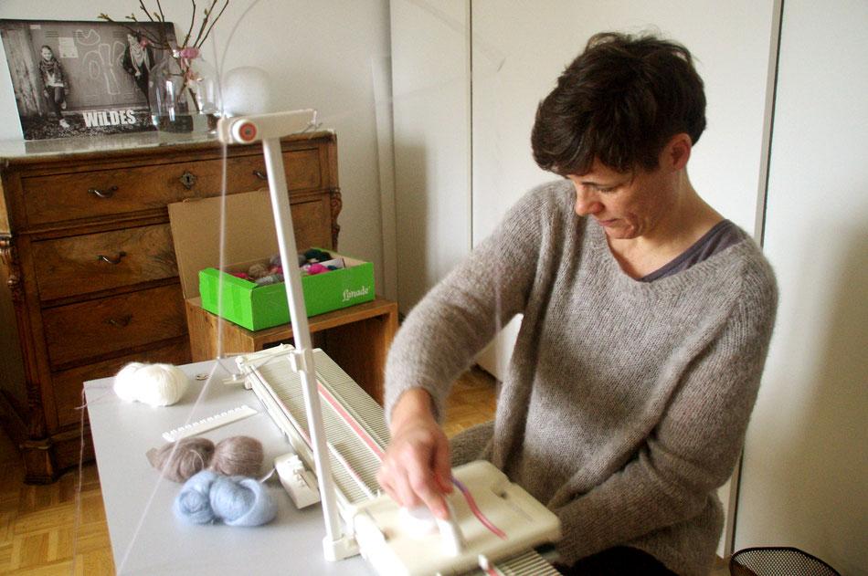 Eva im grauen Strickpulli sitzend rechts im Halbprofil arbeitet an Strickmaschine, die vor ihr steht