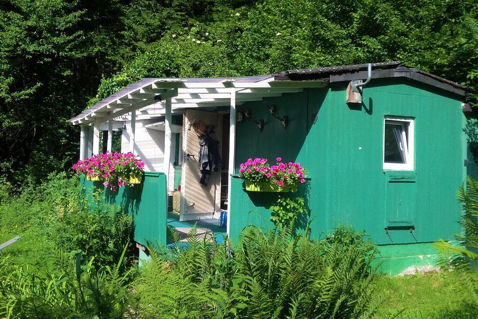 eine grün gestrichene Holzhütte. Davor eine Veranda mit weißen Pfosten und pinken Petunien n Blumenkästen. Um die Hütte Garten